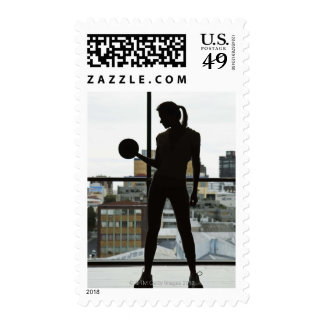 Silhouette of woman lifting weights at gym stamp