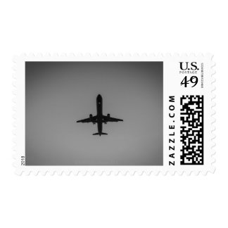 Silhouetted aircraft landing postage stamp