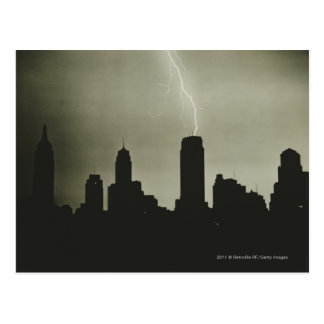 Silhouettes of skyscrapers and lightning in sky postcard
