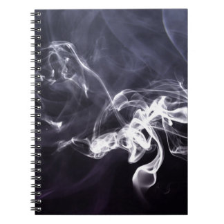 Silhoutte soñador del humo fresco sobre la púrpura libreta