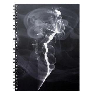 Silhoutte soñador del humo fresco sobre la púrpura libro de apuntes