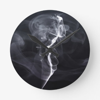 Silhoutte soñador del humo fresco sobre la púrpura reloj de pared