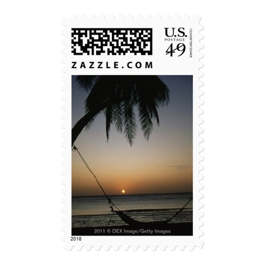 Silhuetted empty hammock at sunset postage