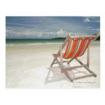 Silla de cubierta en la arena blanca de la playa postal