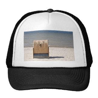 Silla de madera en la playa gorras