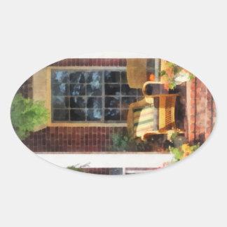 Silla de mimbre con la almohada rayada pegatina ovalada