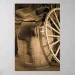 Silla de montar, barril, y rueda de carro poster