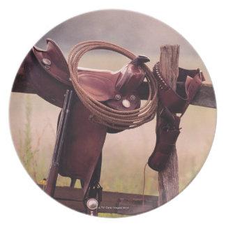 Silla de montar y lazo en la cerca plato de cena