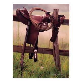 Silla de montar y lazo en la cerca postal
