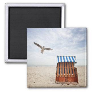 Silla de playa de mimbre en la playa iman de nevera