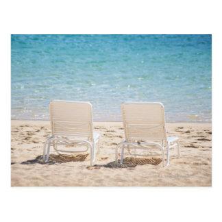 Sillas de cubierta en la playa arenosa postal