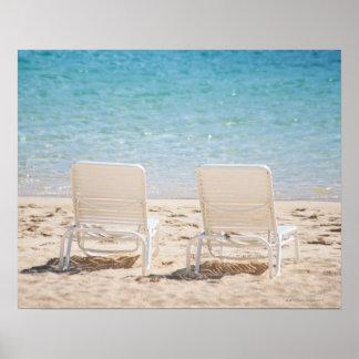 Sillas de cubierta en la playa arenosa póster