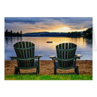 Sillas de madera en la puesta del sol en la playa tarjeta pequeña