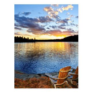 Sillas de madera en la puesta del sol en la playa tarjeta postal