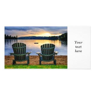 Sillas de madera en la puesta del sol en la playa tarjetas personales