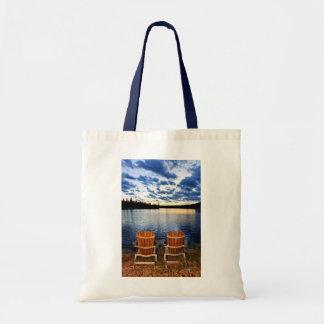 Sillas de madera en la puesta del sol en orilla bolsas