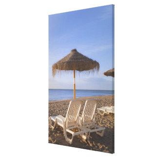 Sillas de playa de la arena con el paraguas impresiones en lona estiradas