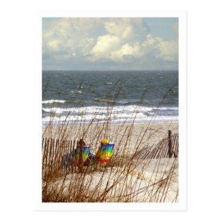 Sillas de playa del arco iris postales