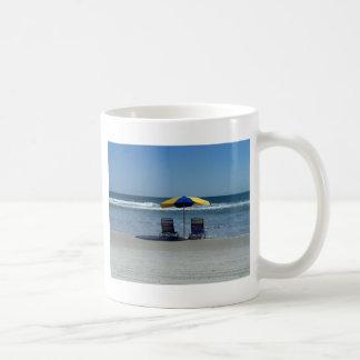 Sillas de playa en la línea de la playa tazas