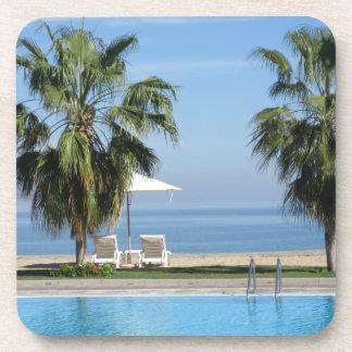 Sillas de playa y paraguas, palmas, océano, posavasos de bebida
