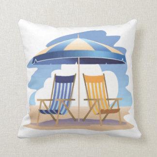 Sillas y paraguas azules y amarillos de playa cojin
