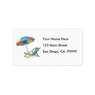Sillas y paraguas de playa de la playa etiquetas de dirección