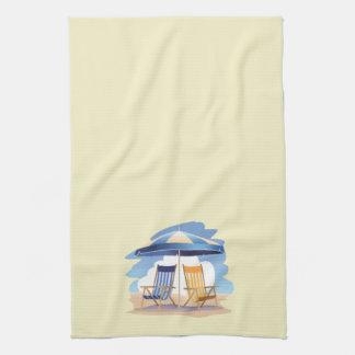 Sillas y paraguas rayados de playa en amarillo toallas