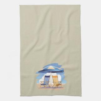 Sillas y paraguas rayados de playa en la crema toallas
