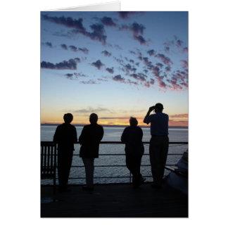 Sillhouettes en la puesta del sol tarjeta de felicitación