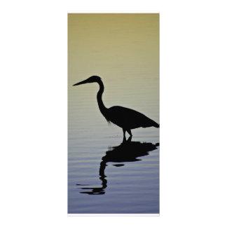 Silueta azul del pájaro de la garza en la puesta d tarjeta publicitaria a todo color