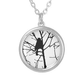 Silueta blanco y negro del chickadee en un árbol colgante redondo
