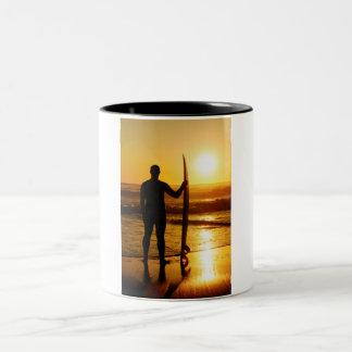 Silueta de la persona que practica surf en la taza de dos tonos