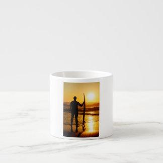 Silueta de la persona que practica surf en la taza espresso