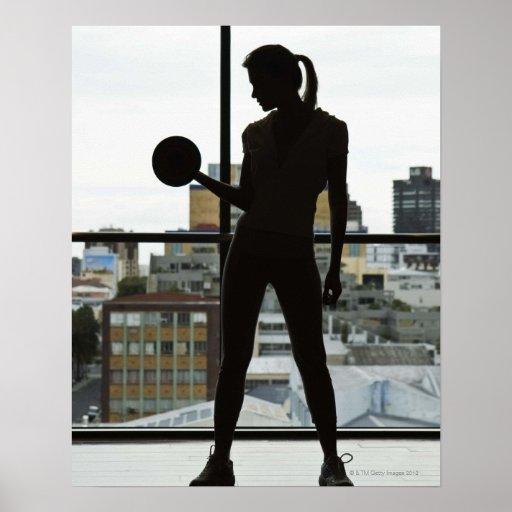 Silueta de los pesos de elevación de la mujer en póster