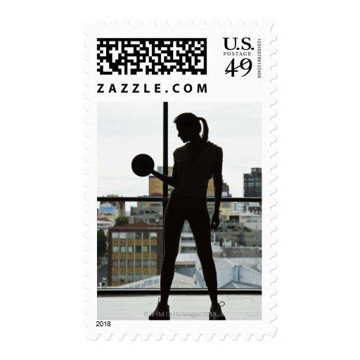 Silueta de los pesos de elevación de la mujer en sello