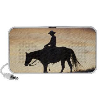 Silueta de una vaquera en su caballo contra laptop altavoces