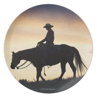 Silueta de una vaquera en su caballo contra platos para fiestas