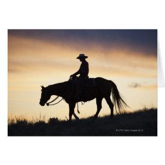 Silueta de una vaquera en su caballo contra tarjeta de felicitación
