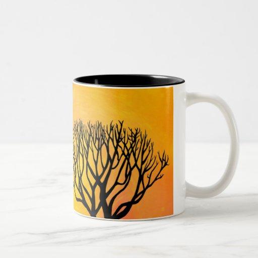 Silueta del árbol (resplandor solar anaranjado) tazas