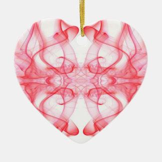 Silueta del extracto del humo coloreado rojo en adorno navideño de cerámica en forma de corazón