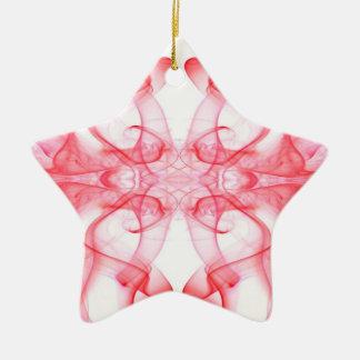 Silueta del extracto del humo coloreado rojo en adorno navideño de cerámica en forma de estrella