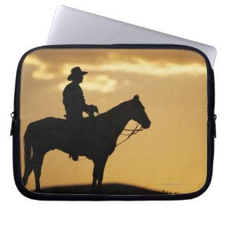 Silueta del vaquero a caballo en la puesta del sol mangas portátiles