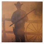 Silueta del vaquero con el rifle a disposición azulejo cuadrado grande