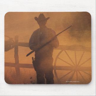 Silueta del vaquero con el rifle a disposición tapetes de ratón