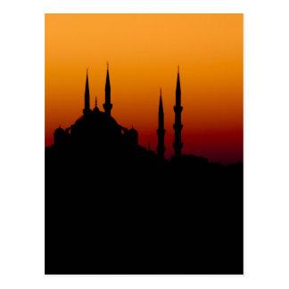 Silueta hermosa de una mezquita en la puesta del postales