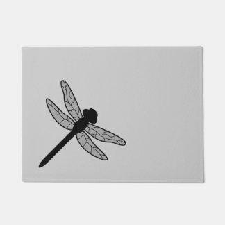 Silueta negra de la libélula en gris felpudo