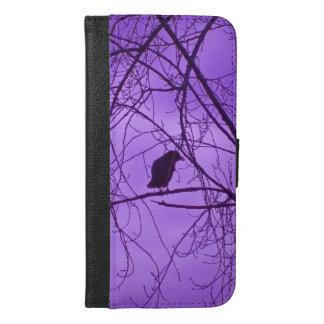 Silueta negra del cuervo que se sienta en rama de