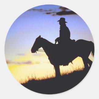 Silueta occidental de la puesta del sol del etiquetas redondas
