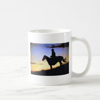 Silueta occidental de la puesta del sol del vaquer tazas
