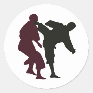 Siluetas de artistas marciales durante una lucha pegatina redonda